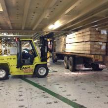 Unloading Lumber inside the decks of a car moving ship.