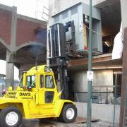 Lifting an Electrical Box into place in New Westminster.